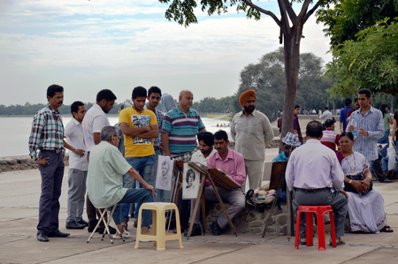 live work city: Tourists getting their portrait made by pencil sketch portrait artists at sukhna lake, Chandigarh, India. Editorial