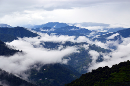 shrouded: A peaceful picturesque misty morning over Himalayan mountain range in Shimla, Himachal Pradesh, India, Asia. Layers of hills are visible emerging from the mist shrouded valley. The mist here rolls in and out constantly. Stock Photo
