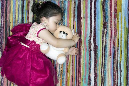 peacefully: Little girl sleeping peacefully with her teddy bear on a colorful rug. Stock Photo