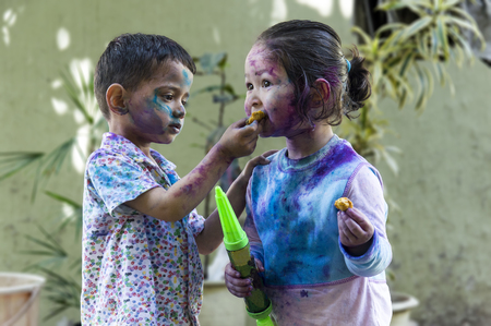 smeared baby: Brother and sister with their face smeared with colors celebrating Holi festival in India.
