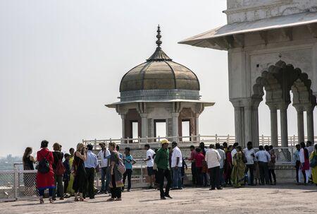 octogonal: Agra, India-11 de octubre de, 2016: Los turistas admirando y posando con Samman Burj torre octogonal y la sala privada Shah Jahan`s Diwan-i-Khas de la antigua fortaleza de Agra, Agra, India. Fuerte de Agra es una obra maestra de arquitectura Mughal. Editorial