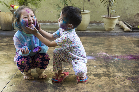 smeared baby: Two Indian kids with their face smeared with colors celebrate Holi, the festival of colors.