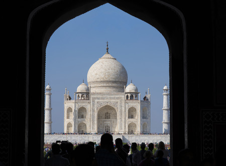 love dome: Taj Mahal viewed through entrance gate and silhouette of people going through entry gate to the Taj Mahal complex in Agra, India. Stock Photo