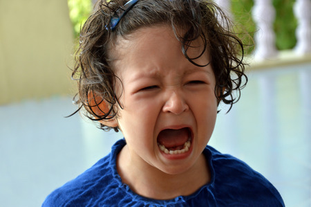 Portrait d'une petite fille en bas âge qui pleure avec la bouche grande ouverte et expression contrariée au visage.