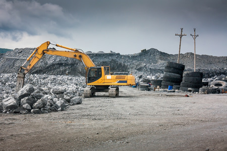 earthwork: Heavy excavator with shovel standing on hill with rocks