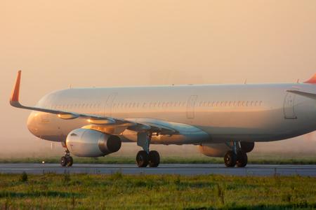 Самолет на рулежной дорожке в начале туманное утро