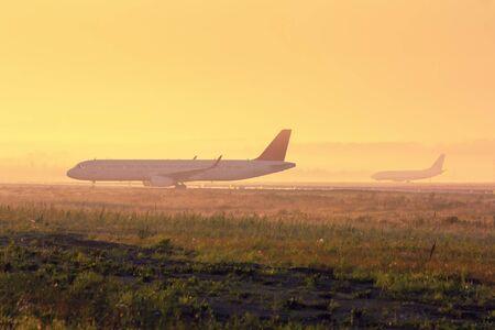 Самолеты на рулежной дорожке в раннем туманное утро