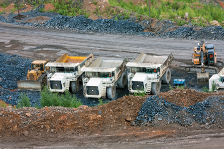 Bulldozer, dump trucks and an excavator at the bottom of the quarry Stock Photo