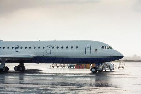 Самолет на перрон под проливным дождем Редакционное