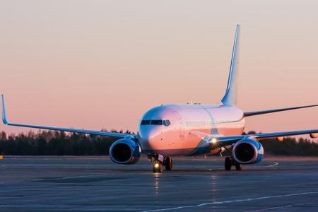 Выруливает самолет в утреннем малиновый Фото со стока