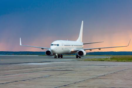 Выруливает самолет рано утром на главной рулежной дорожке на фоне дождя