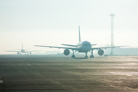 Airplanes in the fog on the airport apron Фото со стока - 67010753