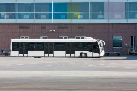 Аэропорт автобус и тележки для багажа рядом с терминалом