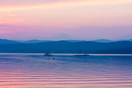 Закат на красивое озеро с яхт Фото со стока
