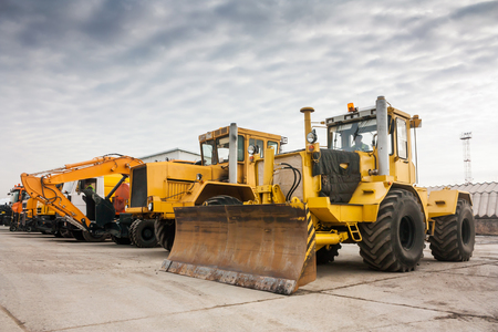Two heavy wheeled tractor one excavator and other construction machinery