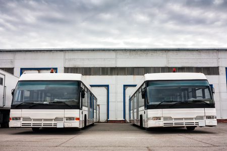 Airport buses in the parking lot near the garages Фото со стока