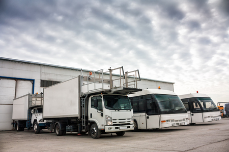 Vliegtuigcateraars en luchthavenbussen op de parkeerplaats bij de garages