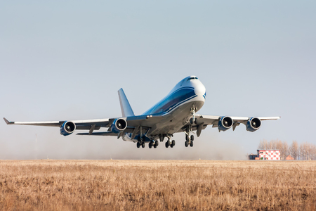Wide body cargo airplane takes off leaving behind a cloud of dust Stock fotó - 93255116
