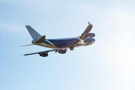 Transport airplane flying backlit