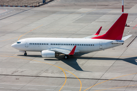Taxiing white and red aircraft on the airport apron Фото со стока
