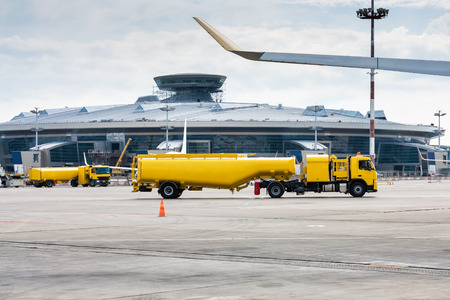 Two yellow tank truck aircraft refuelers at the airport apron Фото со стока
