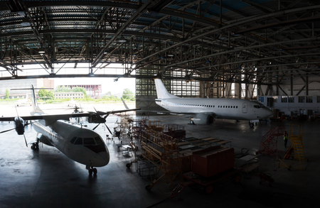 Repair and maintenance of passenger airplanes in the aviation hangar Фото со стока