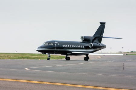 Black business jet taxiing from the runway Standard-Bild