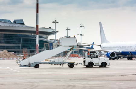 The tractor pulls the passenger boarding stairs at the airport apron beside to the terminal