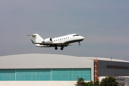 Business jet taking off on the background of a hangar