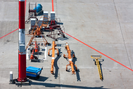 Towbars for different airplanes, aircraft steps and signal cones at the airport apron