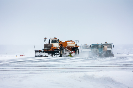 Snowplows cleans the runway Фото со стока - 93897636