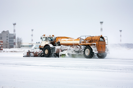 Airfield sweeper cleans the taxiway at the cold winter airport