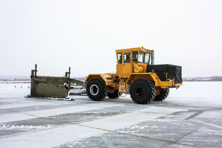 Heavy tractor cleans the runway from snow Фото со стока - 93939962