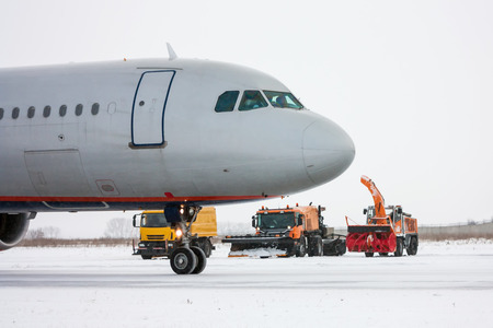 Airliner and snow removal equipment in a cold winter airport Фото со стока