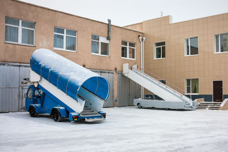 Passenger boarding steps vehicles nearby garages at the cold winter airport Фото со стока - 93920152