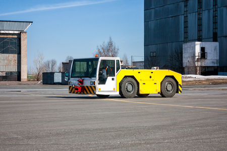 Aircraft tow tractor moves beside to the hangars Фото со стока