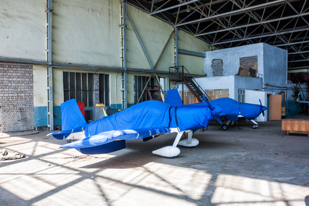 Two shrouded small sports aircraft in a hangar Фото со стока