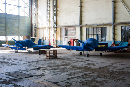 Two shrouded small sports airplanes in a hangar
