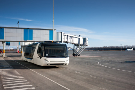 Bus at the airport apron near passenger boarding bridge Фото со стока - 93867672