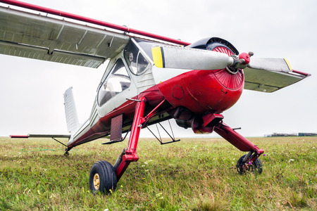 Small sports airplane for towing gliders stands on the grass Фото со стока