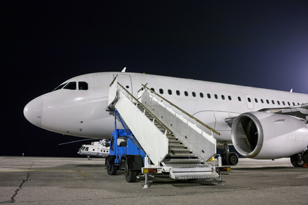 Airplane and passenger boarding steps vehicle at the night airport apron Фото со стока