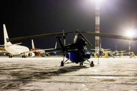 Rear view of the helicopter and passenger airplanes on the airport apron at winter night Фото со стока - 95181222