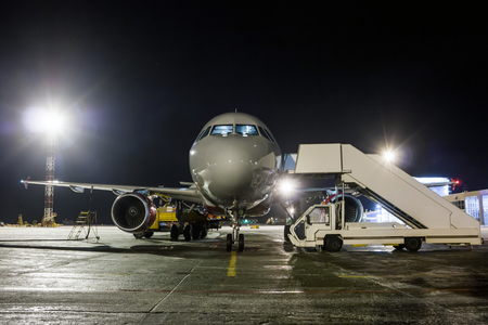 Front view of ground handling passenger airplane at night Фото со стока - 94838765