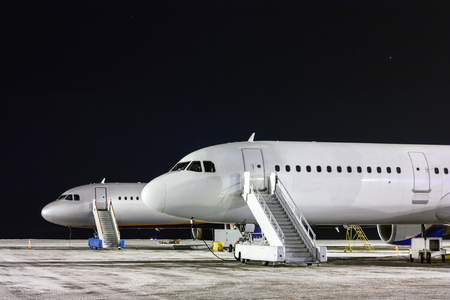 The front part of the two aircraft with passenger boarding stairs at night winter airport apron Фото со стока - 94822934