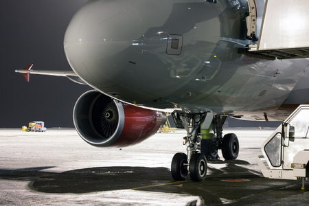 Nose, engine and landing gears of passenger airplane at the night airport apron Фото со стока - 95072584
