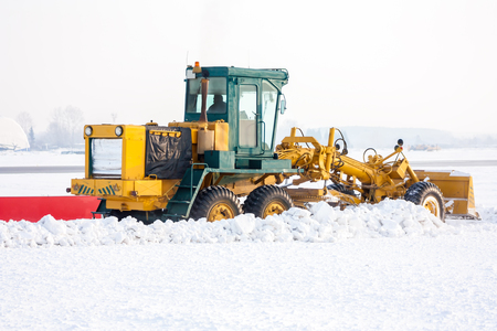 Grader clears snow from the taxiway at the airport Фото со стока - 94838773