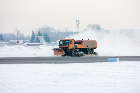 Snow-removal machine cleans the main taxiway at the airport Фото со стока - 94895569