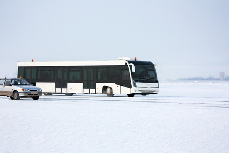 Airport bus and car on the winter apron Фото со стока - 94838790