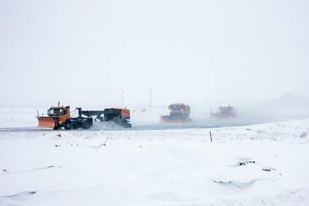 Snowplows cleans the taxiway at the airport Фото со стока - 95072585