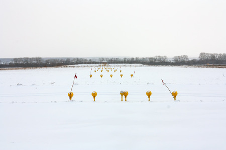 Approach lights of the winter airport runway from the back side Фото со стока - 95043825